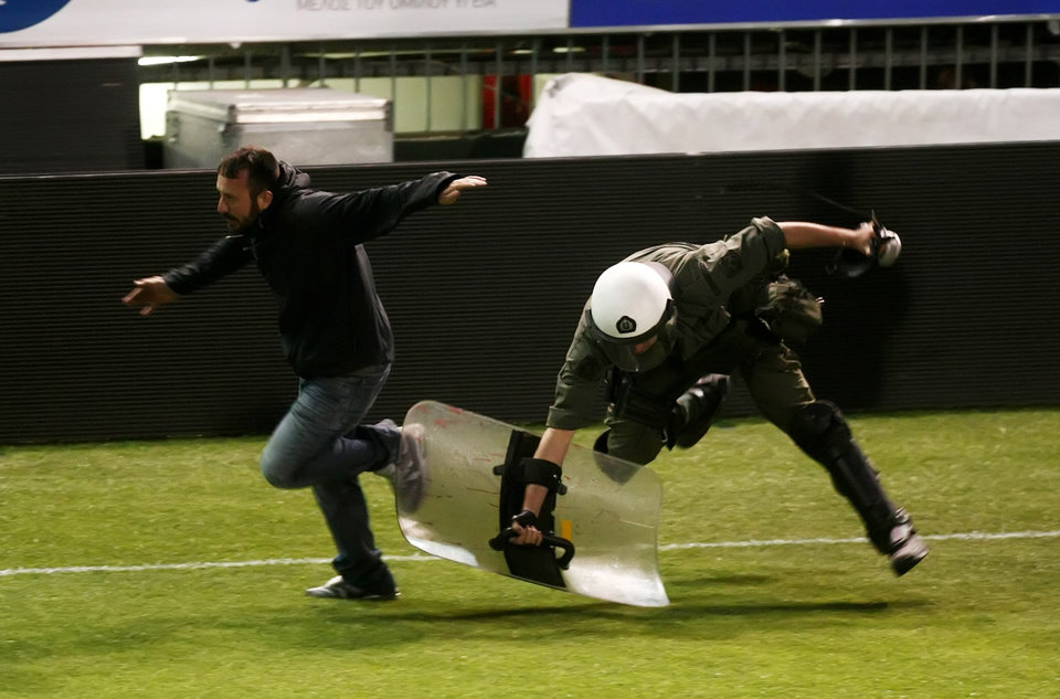 Photo - A fan runs to avoid a riot policeman during clashes shortly before the start of the Greek championship play-off match between Panathinaikos and PAOK at Apostolos Nikolaidis stadium in Athens, Sunday, May 4, 2014. (AP Photo/InTime Sports)  GREECE OUT