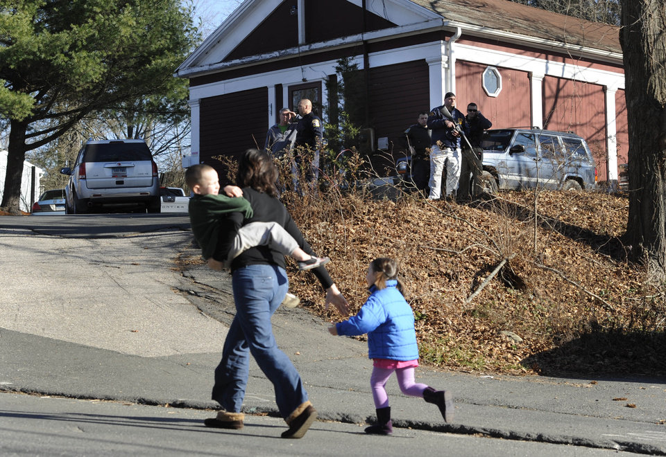 FILE - In this Friday, Dec. 14, 2012 file photo, a mother runs with her children as police above canvass homes in the area following a shooting at the Sandy Hook Elementary School in Newtown, Conn., where Adam Lanza fatally shot 27 people, including 20 children. Psychiatrists say after the grief and fear fades, most of Newtown\'s young survivors probably will cope without long-term emotional problems, often through play. Among the challenges will be spotting which children are struggling enough that they may need professional help. (AP Photo/Jessica Hill, File)