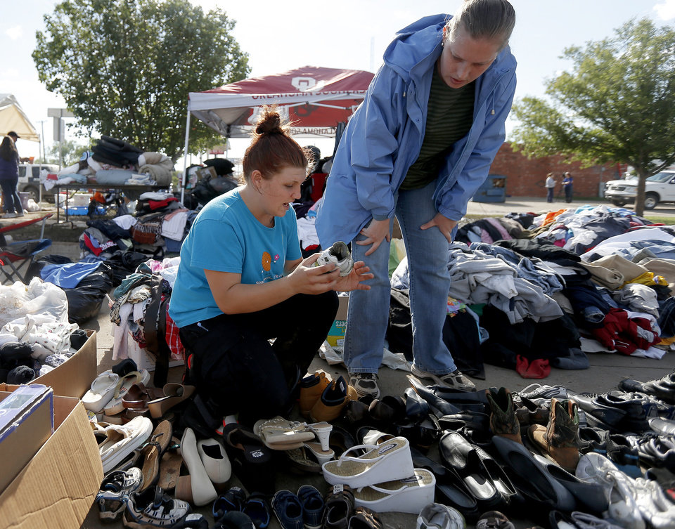 Photo - Volunteer Shelby Hays helps tornado victim Amber Kelley choose shoes for her children outside the Plaza Towers neighborhood in Moore, Okla., on Wednesday, May 22, 2013.A tornado damaged the area on Monday, May 20, 2013. Photo by Bryan Terry, The Oklahoman