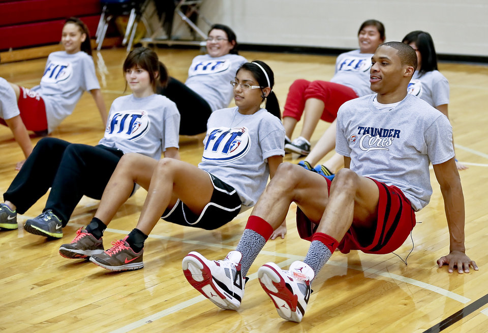 Photo - THUNDER FIT / NBA BASKETBALL TEAM: Russell Westbrook works out with students during a visit by the Oklahoma City Thunder to U.S. Grant High School to promote physical fitness on Monday, Jan. 28, 2013, in Oklahoma City, Okla.  Photo by Chris Landsberger, The Oklahoman