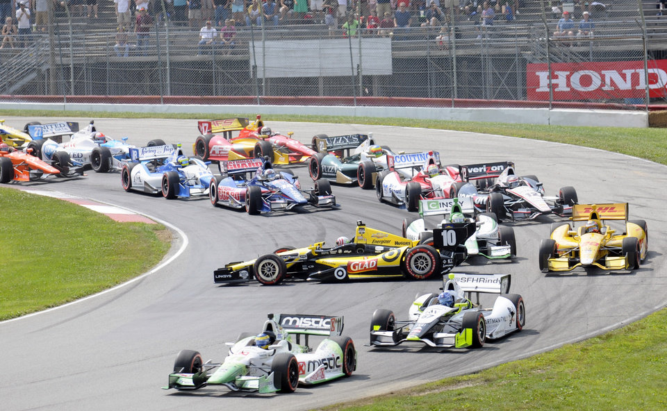 Photo - Sebastien Bourdais, of France, leads Josef Newgarden as Tony Kanaan (10), of Brazil, gets spun out behind them on the first lap during the IndyCar Honda Indy 200 auto racing at Mid-Ohio Sports Car Course in Lexington, Ohio Sunday, Aug. 3, 2014. (AP Photo/Tom E. Puskar)