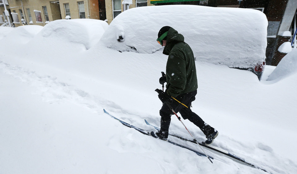 Photo - Mike Brown, of Boston, cross country skis past snow covered cars through the Chinatown neighborhood of Boston, Saturday, Feb. 9, 2013. The Boston area received about two feet of snow from a winter storm. (AP Photo/Charles Krupa)