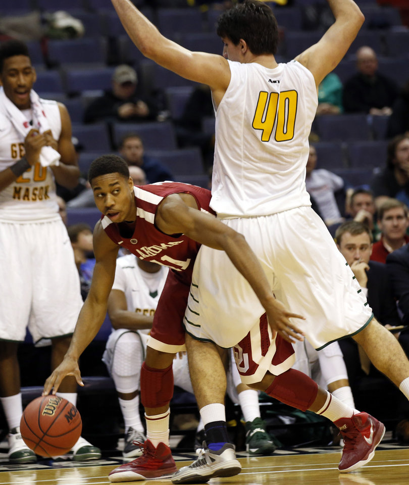 Photo - Oklahoma guard Isaiah Cousins (11) works to get around George Mason forward Marko Gujanicic (40) during the second half of an NCAA college basketball game in the BB&T Classic, Sunday, Dec. 8, 2013, in Washington. Oklahoma won 81-66. (AP Photo/Alex Brandon)