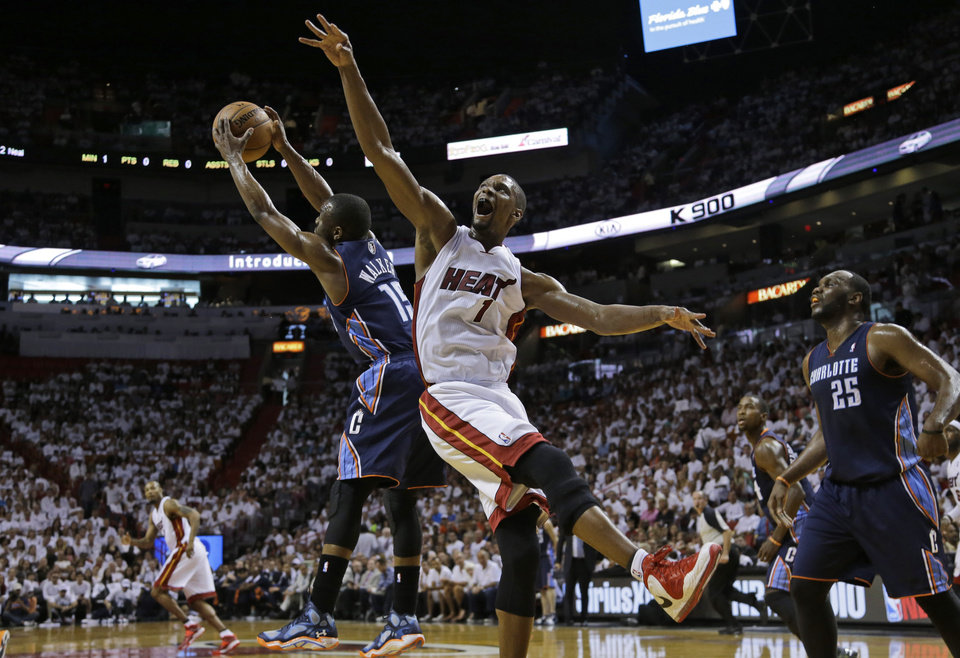 Photo - Charlotte Bobcats' Kemba Walker (15) grabs a rebound over Miami Heat's Chris Bosh (1)during the first half in Game 1 of an opening-round NBA basketball playoff series, Sunday, April 20, 2014, in Miami. (AP Photo/Lynne Sladky)