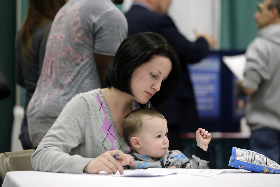 Photo - In this April 22, 2014 photo, Sarah Keegan of Windham, N.Y., with her son Kevin, fills out paperwork during a job fair at Columbia-Greene Community College in Hudson, N.Y. The Labor Department on Friday, May 2, 2014 said U.S. employers added a robust 288,000 jobs in April, the most in two years, the strongest evidence to date that the economy is picking up after a brutal winter slowed growth. (AP Photo/Mike Groll)