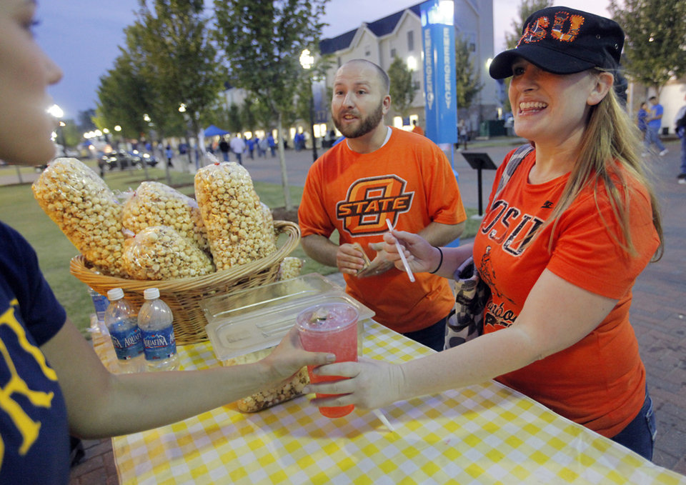 Photo - Brett and Lauren Manis, of Edmond, buy items from the concession stand before Oklahoma State and Tulsa squared off on Saturday. Photo by Chris Landsberger, The Oklahoman
