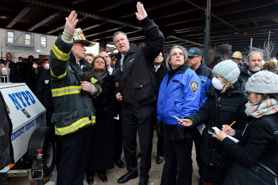 Photo - New York City Mayor Bill de Blasio, center, talks with first responders near the site of a gas leak-triggered explosion in East Harlem, Thursday, March 13, 2014, in New York. Rescuers working amid gusty winds, cold temperatures and billowing smoke pulled additional bodies Thursday from the rubble of two apartment buildings that collapsed Wednesday. (AP Photo/The Daily News, Marcus Santos, Pool)