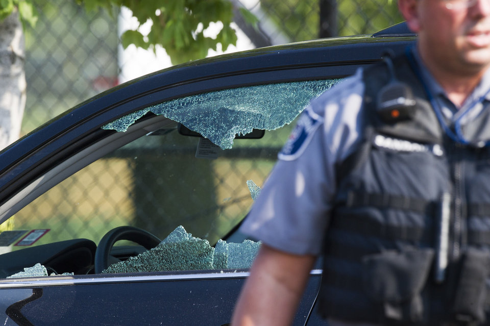 Photo - A police officer stands by an automobile with a damaged driver's window at the scene of a multiple shooting in Alexandria, Va., Wednesday, June 14, 2017, where House Majority Whip Steve Scalise of La. was shot.  (AP Photo/Cliff Owen)