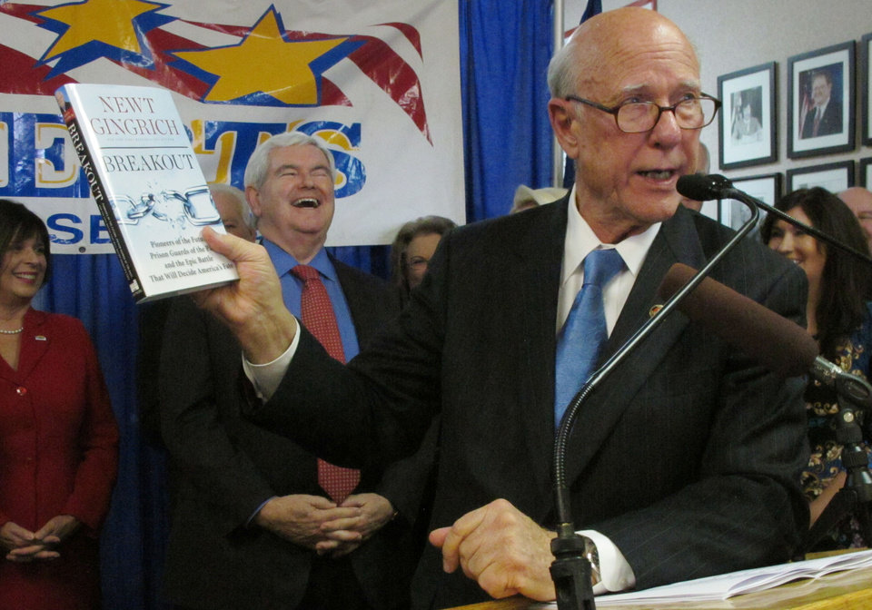 Photo - Kansas Sen. Pat Roberts shows off a copy of former U.S. House Speaker Newt Gingrich's latest book as Gingrich laughs at his remarks in the background, Friday, Nov. 8, 2013, in Overland Park, Kan. Gingrich is supporting Roberts' re-election. (AP Photo/John Hanna)