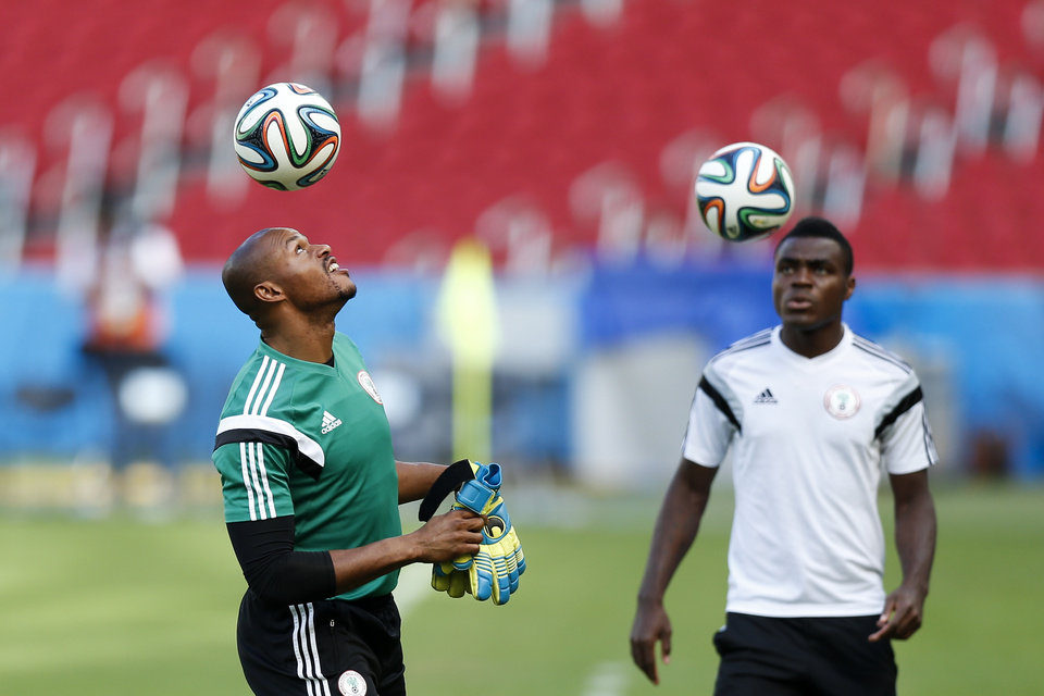 Photo - Nigeria's goalkeeper Austin Egide, left, heads the ball during a training session at Beira-Rio Stadium in Porto Alegre, Brazil, Tuesday, June 24, 2014.  Nigeria plays in group F of the 2014 soccer World Cup. (AP Photo/Victor R. Caivano)