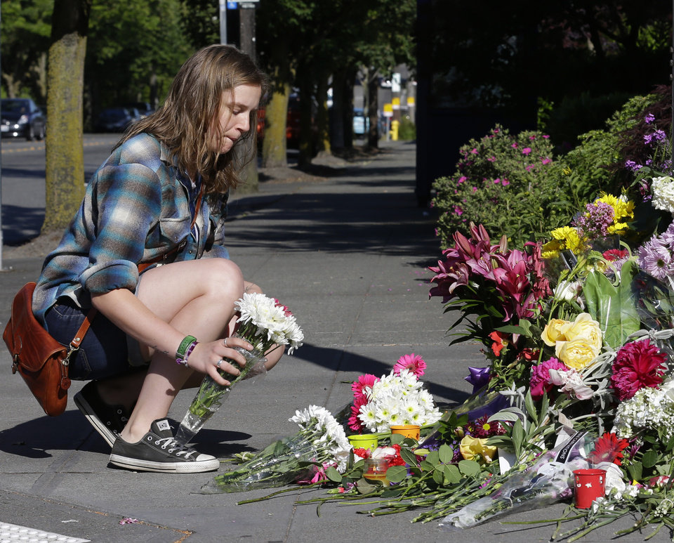 Photo - Chelsea Yarbro, a senior in apparel design at Seattle Pacific University, places flowers at a memorial near Otto Miller Hall, Friday, June 6, 2014 in Seattle, where a shooting took place. A 19-year-old man was fatally shot and two other young people were wounded after the gunman entered the foyer of a Seattle Pacific University building and started shooting Thursday afternoon.  (AP Photo/Ted S. Warren)