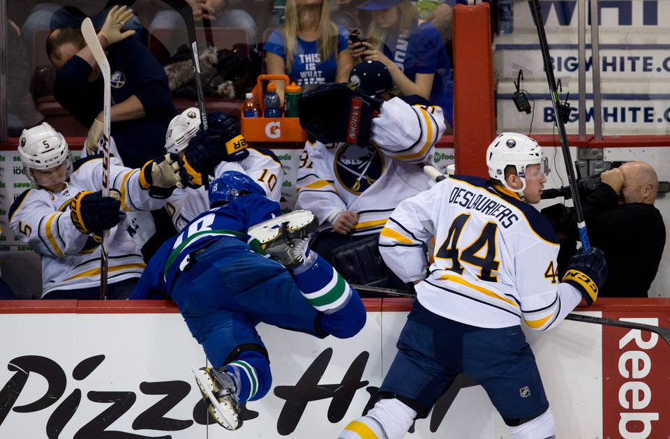 Photo - Buffalo Sabres' Nicolas Deslauriers, right, checks Vancouver Canucks' Ryan Stanton, left, into the Sabres' bench as, from left, Chad Ruhwedel,  Christian Ehrhoff, of Germany, and goalie Matt Hackett get out of the way during second period NHL hockey action in Vancouver, British Columbia, on Sunday March 23, 2014. (AP Photo/The Canadian Press, Darryl Dyck)