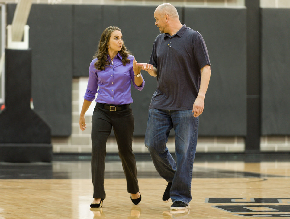 Photo - WNBA star Becky Hammon, left, speaks with Tom James, Director of Communications for the San Antonio Spurs while walking to a media availability at the Spurs practice facility Tuesday, Aug. 5, 2014, in San Antionio, Texas. The San Antonio Spurs hired WNBA star Becky Hammon on Tuesday, making her the first full-time, paid female assistant on an NBA coaching staff.  (AP Photo/Bahram Mark Sobhani)