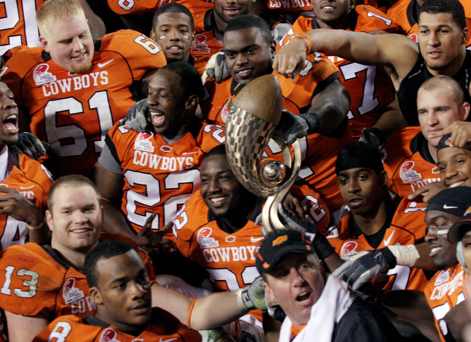 Photo - OKLAHOMA STATE UNIVERSITY / OSU / COLLEGE FOOTBALL / INSIGHT BOWL: Oklahoma State players and head coach Mike Gundy pose with the trophy after defeating Indiana 49-33 at the Insight Bowl college football game, Monday, Dec. 31, 2007 in Tempe, Ariz. (AP Photo/Mary Schwalm)  ORG XMIT: PNS115