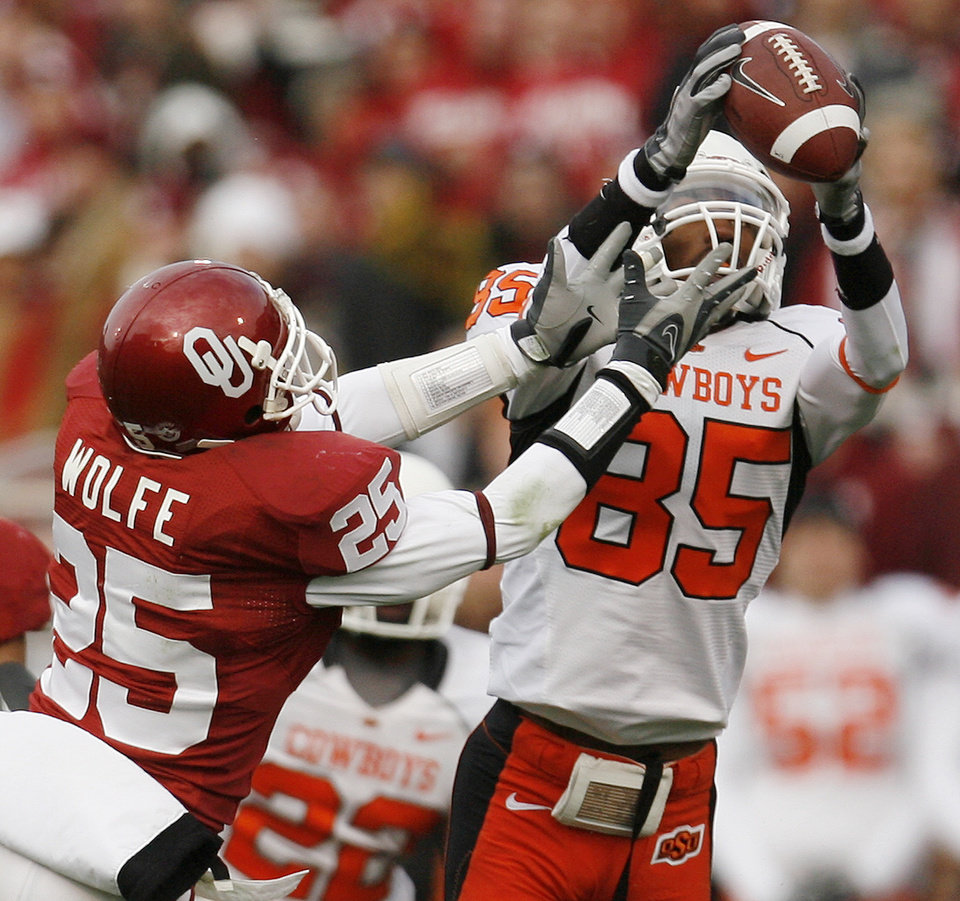 Photo - OSU's Damian Davis catches a pass in front of D.J. Wolfe of OU during the first half of the college football game between the University of Oklahoma Sooners (OU) and the Oklahoma State University Cowboys (OSU) at the Gaylord Family-Memorial Stadium on Saturday, Nov. 24, 2007, in Norman, Okla.  Photo By Bryan Terry, The Oklahoman