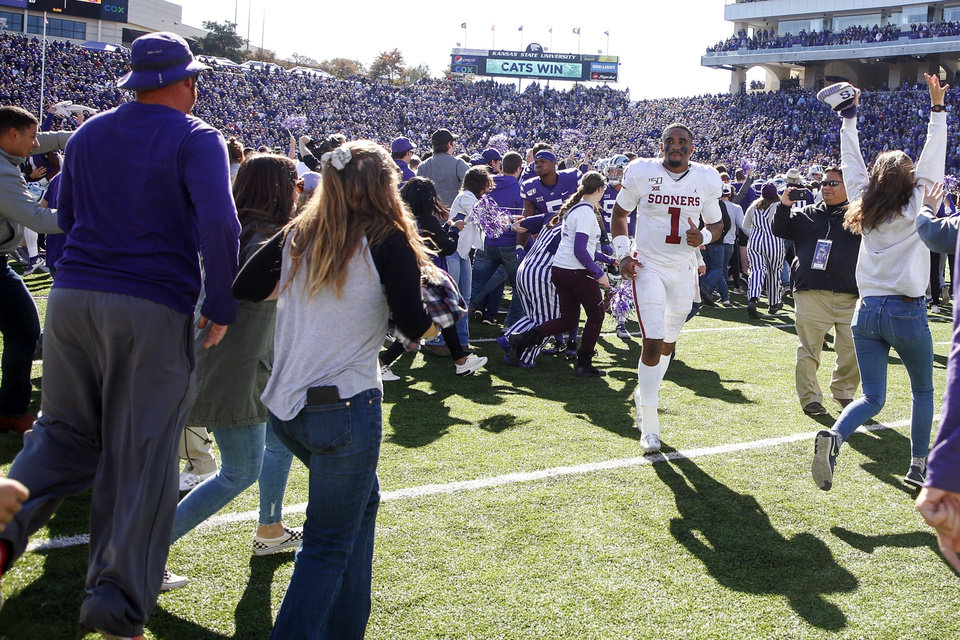 Photo - Kansas State fans storm the field as Oklahoma quarterback Jalen Hurts (1) attempts to head towards the locker room after the Sooners loss to the Wildcats in an NCAA football game at Bill Snyder Family Stadium in Manhattan, Kan., Saturday, Oct. 26, 2019. (Ian Maule/Tulsa World via AP)