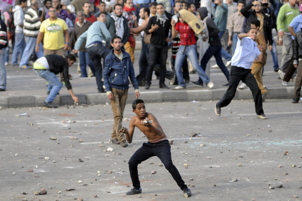 Protesters hurl stones during clashes between supporters and opponents of President Mohammed Morsi in Alexandria, Egypt, Friday, Nov. 23, 2012. Opponents and supporters of Mohammed Morsi clashed across Egypt on Friday, the day after the president granted himself sweeping new powers that critics fear can allow him to be a virtual dictator. Thousands from the two camps threw stones and chunks of marble at each other outside a mosque in the Mediterranean city of Alexandria after Friday Muslim prayers.(AP Photo/Tarek Fawzy)