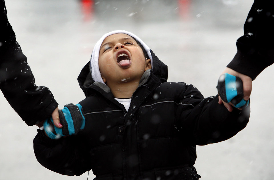 Roberto Alvarez, 3, tries to catch snowflakes as he walks with his mother, Bianca Peregrina, right, and cousin, Paul Rocha, Monday, Feb. 25, 2013, in Kansas City, Mo. (AP Photo/The Kansas City Star, Keith Myers)