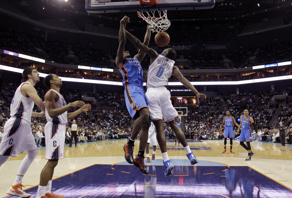 Photo - Oklahoma City Thunder's Serge Ibaka (9) dunks agaisnt Charlotte Bobcats' Bismack Biyombo (0) during the first half of an NBA basketball game in Charlotte, N.C., Friday, March 8, 2013. (AP Photo/Bob Leverone) ORG XMIT: NCBL104