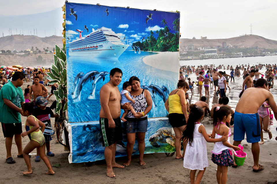 Photo - In this March 3, 2013 photo, Karina Alvarado and David Enriquez pose for a picture with their daughter at Agua Dulce beach in Lima, Peru. For five Peruvian soles or about two U.S. dollars beachgoers can pose for a photo to record their day at the beach, in front of backdrops of their choice that include forest landscapes, exotic beach scenes or atop horses. (AP Photo/Rodrigo Abd)