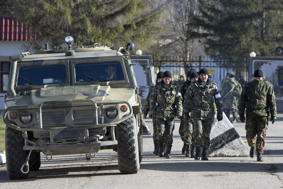 Photo - Ukrainian troops with white bands on their sleeves march past an unmarked Russian military vehicle outside a Ukrainian military base in Perevalne, Crimea, Ukraine, Monday, March 17, 2014. Crimea held a referendum Sunday, in which an overwhelming majority voted for breaking off from Ukraine and joining Russia. (AP Photo/Andrei Udovichenko)
