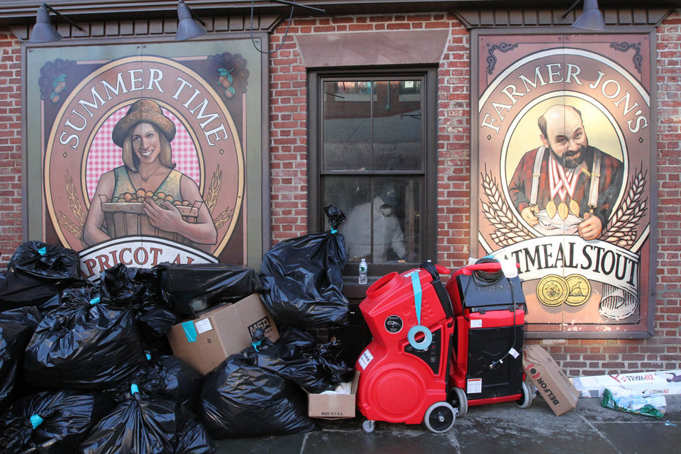 In this Friday, Nov. 23, 2012 photo, a worker wearing protective clothing, behind window, works inside the Heartland Brewery at New York's South Street Seaport, as bags of garbage from the Superstorm Sandy cleanup sit out front. The South Street Seaport, a popular tourist destination, remains a ghost town since the storm. (AP Photo/Tina Fineberg)
