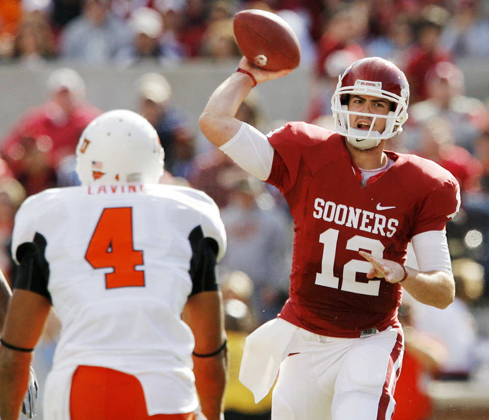 Photo - OU's Landry Jones (12) passes as Patrick Lavine (4) defends for OSU during the first half of the Bedlam college football game between the University of Oklahoma Sooners (OU) and the Oklahoma State University Cowboys (OSU) at the Gaylord Family-Oklahoma Memorial Stadium on Saturday, Nov. 28, 2009, in Norman, Okla.