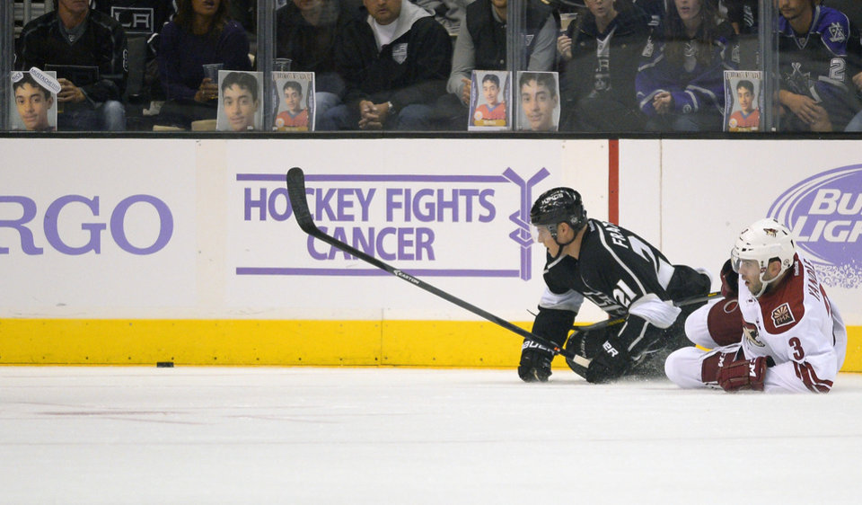 Photo - Los Angeles Kings right wing Matt Frattin, left, and Phoenix Coyotes defenseman Keith Yandle, right, battle for the puck during the first period of their NHL hockey game on Thursday, Oct. 24, 2013, in Los Angeles. (AP Photo/Mark J. Terrill)