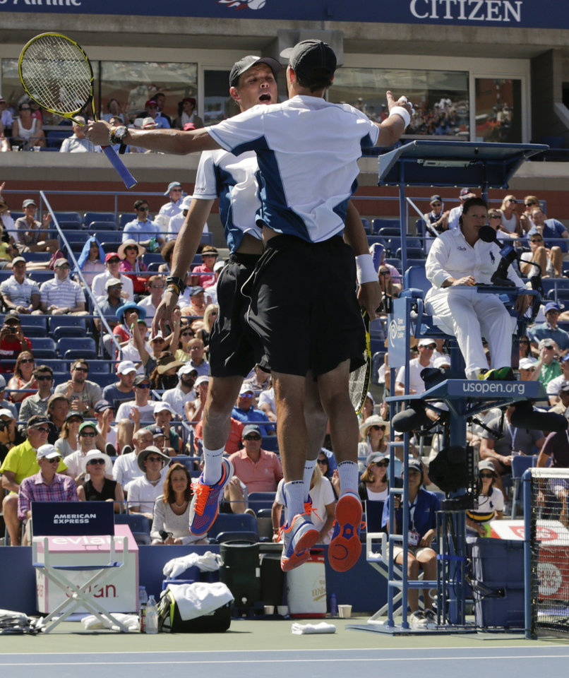 Photo - Bob, left, and Mike Bryan react after defeating Scott Lipsky and Rajeev Ram in a semifinal doubles match during the 2014 U.S. Open tennis tournament, Thursday, Sept. 4, 2014, in New York. (AP Photo/Julio Cortez)