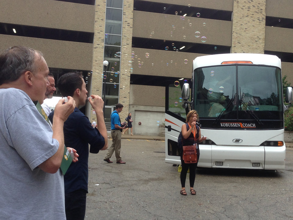 Photo - Joseph Klein, left, and Matt Antoncyzk blow bubbles as a bus carrying gay couples and their supporters prepares to depart Monday, Aug. 25, 2014, in Milwaukee. Couples are heading to Chicago to listen to arguments Tuesday before a federal appeals court. (AP Photo/M.L. Johnson)