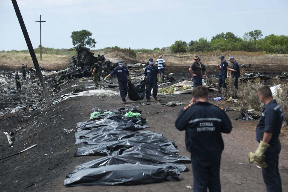 Photo - Ukrainian Emergency workers carry a victim's body in a bag as pro-Russian fighters stand in guard at the crash site of Malaysia Airlines Flight 17 near the village of Hrabove, eastern Ukraine, Sunday, July 20, 2014. Rebels in eastern Ukraine took control Sunday of the bodies recovered from downed Malaysia Airlines Flight 17, and the U.S. and European leaders demanded that Russian President Vladimir Putin make sure rebels give international investigators full access to the crash site.(AP Photo/Evgeniy Maloletka)