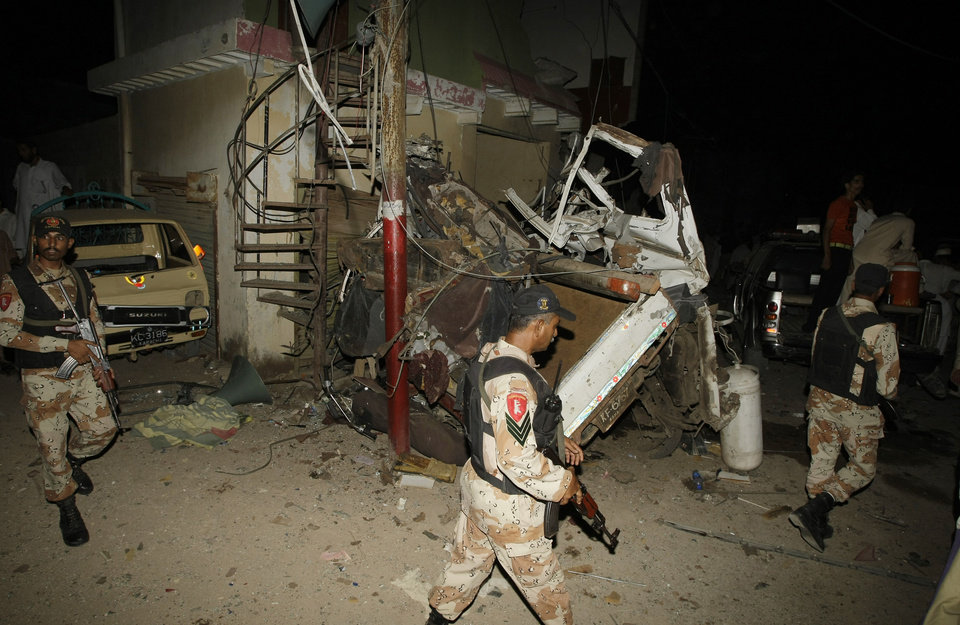 Photo - Pakistani para-military troops cordon off the area of an explosion in Karachi, Pakistan Friday, April 26, 2013.  A bomb planted near the office of a political party threatened by the Taliban has killed many people in southern Pakistan, police said. (AP Photo/Fareed Khan)