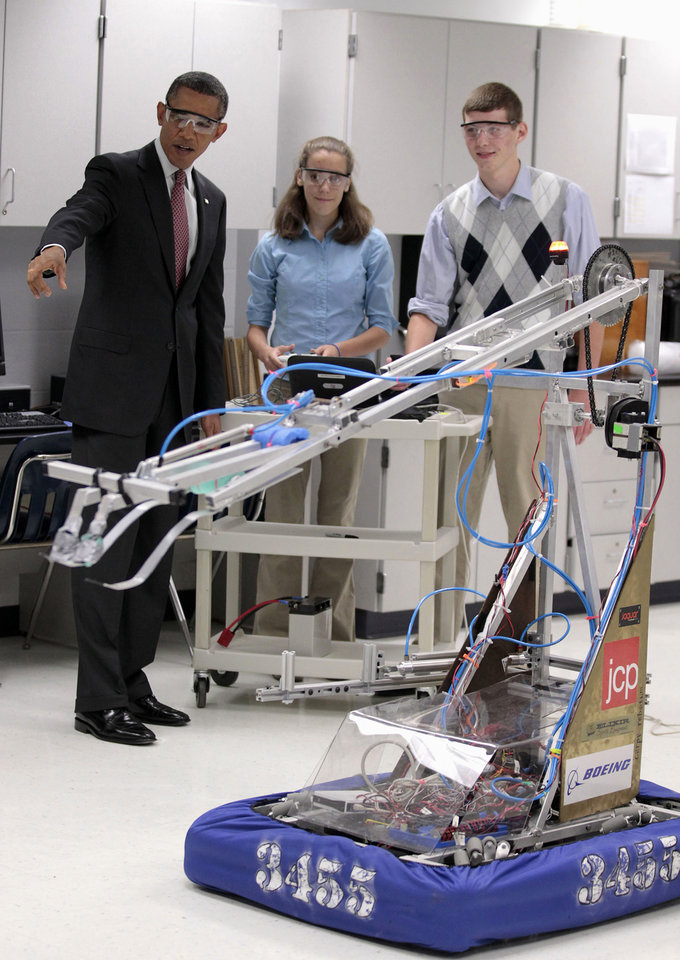 Photo -   FILE - In this Sept. 16, 2011 file photo, President Barack Obama, with students Meghan Clark, center, and Nathan Hughes, right, watches as they demonstrate their FIRST Robot, during a visits to a classroom at Thomas Jefferson High School for Science and Technology in Alexandria, Va. America's decision to re-elect President Barack Obama over Republican presidential candidate, former Massachusetts Gov. Mitt Romney will impact key sectors of the American economy. During the President's first term, Obama signed into law the America Invents Act to streamline the U.S. patent process. The idea was that inventors and entrepreneurs could turn their ideas into products more quickly and create inexpensive ways to resolve disputes(AP Photo/Pablo Martinez Monsivais, File)