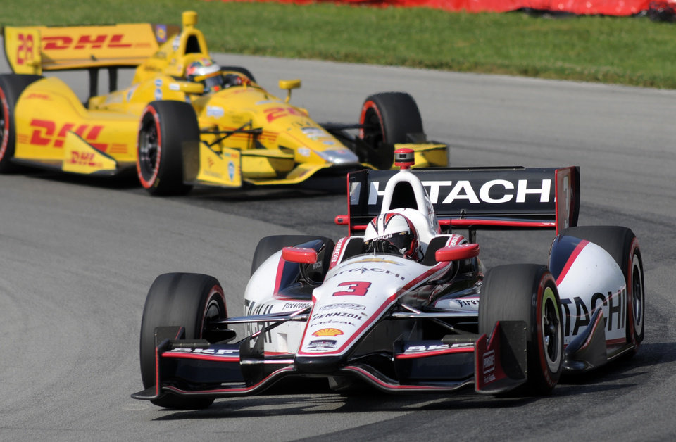 Photo - Helio Castroneves, of Brazil, goes through a corner ahead of Ryan Hunter-Reay during the IndyCar Honda Indy 200 auto racing at Mid-Ohio Sports Car Course in Lexington, Ohio Sunday, Aug. 3, 2014. (AP Photo/Tom E. Puskar)