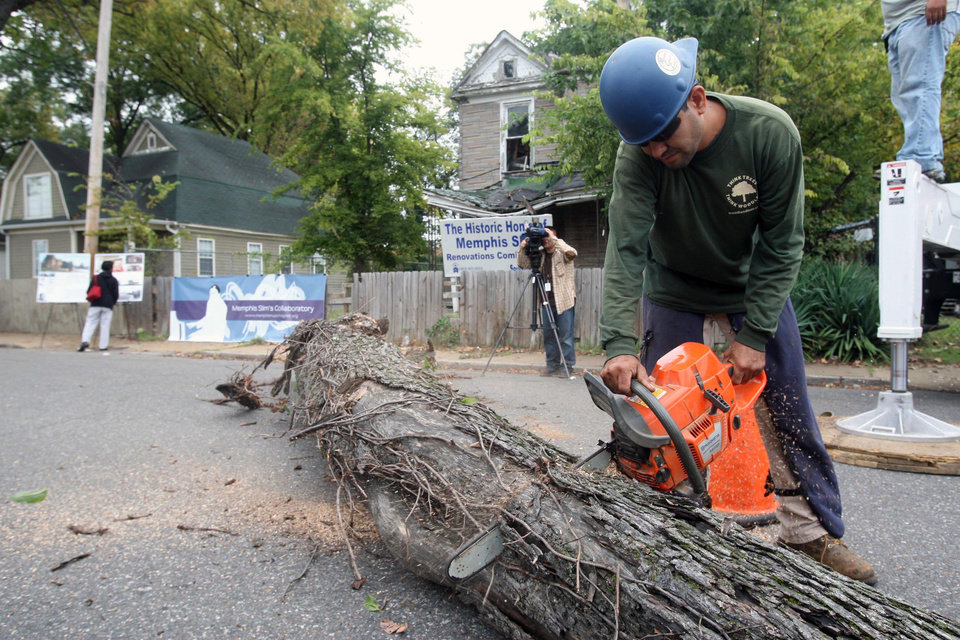 Friday morning, Oct. 12, 2012 the Soulsville USA community witnessed the first steps in the restoration of Memphis Slim\'s house, as Daniel Hernandez cuts a downed tree that was leaning on the structure in Memphis, Tenn. (AP Photo/The Commercial Appeal, Mike Maple)