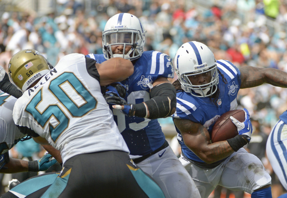 Photo - Indianapolis Colts running back Trent Richardson, right, gets a block from fullback Stanley Havili, center, as he runs past Jacksonville Jaguars outside linebacker Russell Allen (50) for a 1-yard touchdown during the first half of an NFL football game in Jacksonville, Fla., Sunday, Sept. 29, 2013.(AP Photo/Phelan M. Ebenhack)