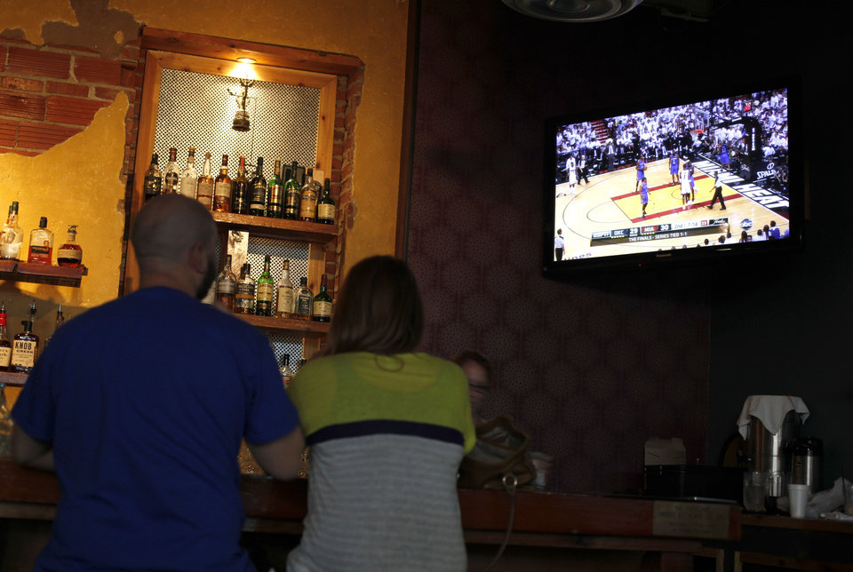 Photo - People watch the Thunder play Miami in the NBA Finals on television at Saint's Pub in Oklahoma City, Sunday, June 17, 2012. Photo by Sarah Phipps, The Oklahoman  SARAH PHIPPS - SARAH PHIPPS