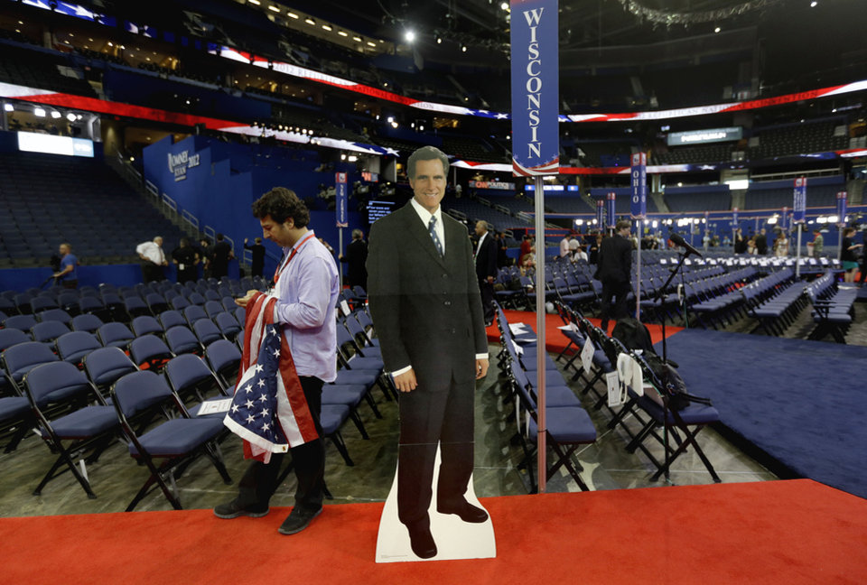 Photo -   A cardboard cutout of Republican presidential nominee, former Massachusetts Gov. Mitt Romney stands on the floor of the Republican National Convention as a member of a German television crew works at left, Wednesday, Aug. 29, 2012, in Tampa, Fla. (AP Photo/David Goldman)