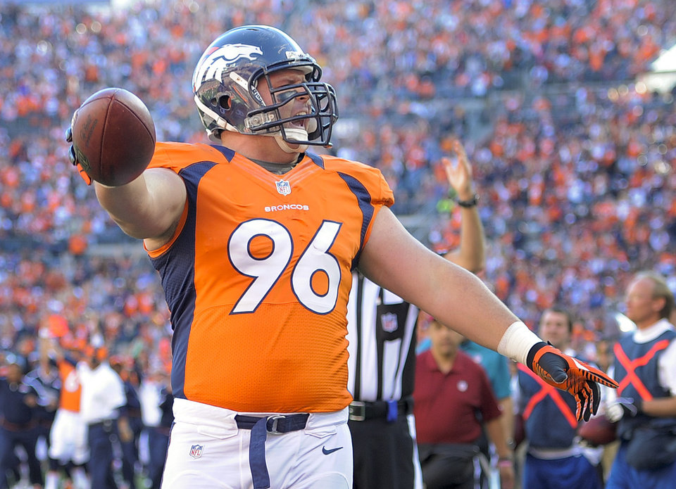 Photo - Denver Broncos defensive tackle Mitch Unrein (96) reacts after scoring a touchdown against the Tampa Bay Buccaneers in the first quarter of an NFL football game, Sunday, Dec. 2, 2012, in Denver. (AP Photo/Jack Dempsey)
