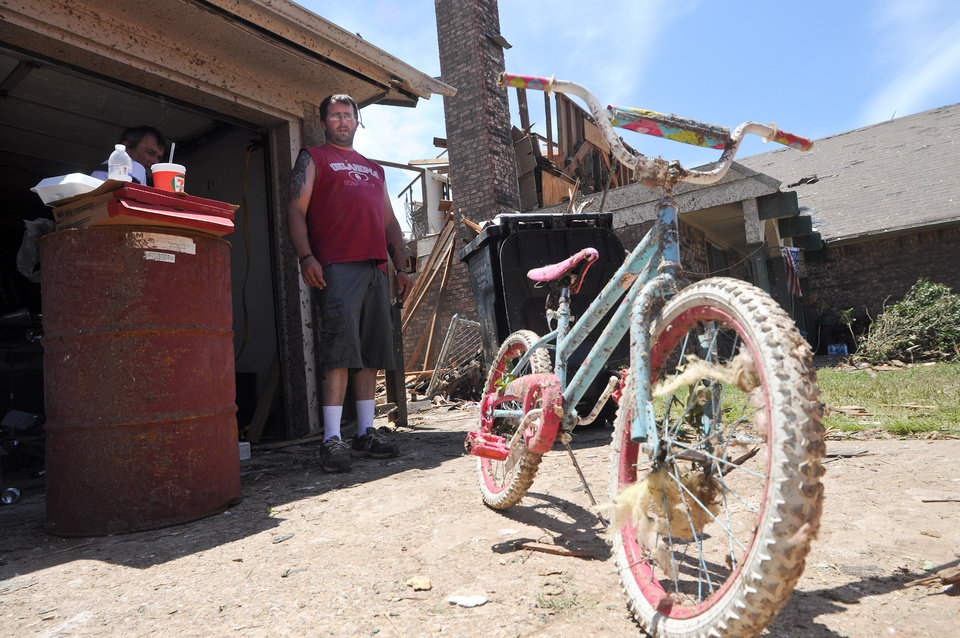 Photo - Michael Roberts surveys the damage to his daughter Addyson Robert's second bicycle that was damaged by the May 20, 2013 tornado that struck Moore, Okla. Photo by KT King, The Oklahoman