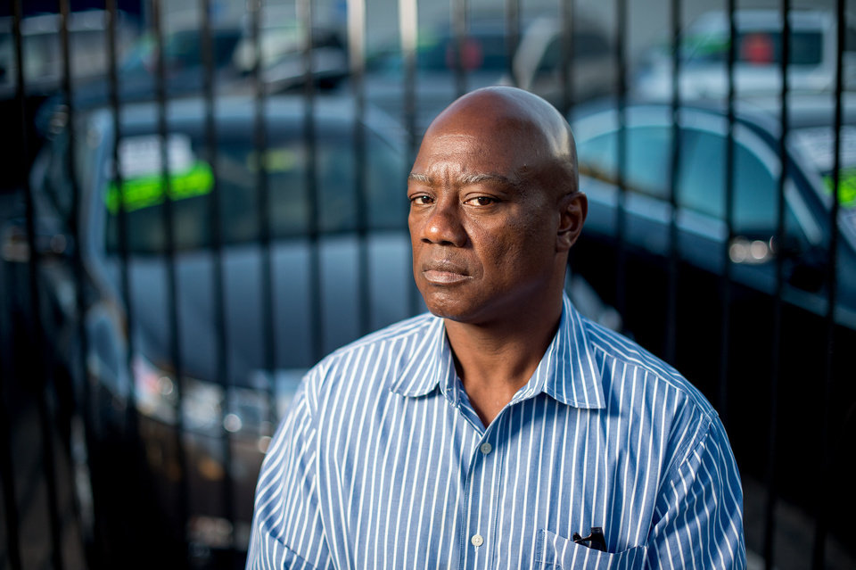 Photo - Arthur Scott, who was paroled in March 2014 after serving time on his 22nd auto theft conviction, stands in front of an Oakland, Calif., Acura dealership on Tuesday, June 24, 2014. Scott, determined to stay out of jail and currently working while taking vocational classes, says he had stolen more than five cars from the dealership. (AP Photo/Noah Berger)