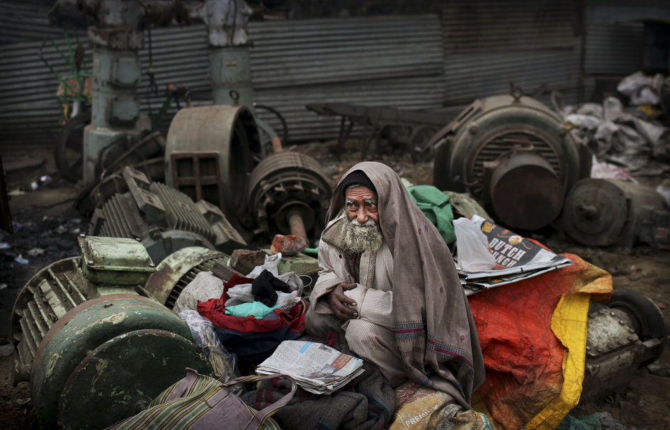 An Indian ragpicker is wrapped in a blanket as he sits in a market on a cold morning in New Delhi, India, Monday, Jan. 7, 2013. North India continues to face below average weather conditions with dense fog affecting flights and trains. More than 100 people have died of exposure as northern India deals with historically cold temperatures. (AP Photo/Kevin Frayer)
