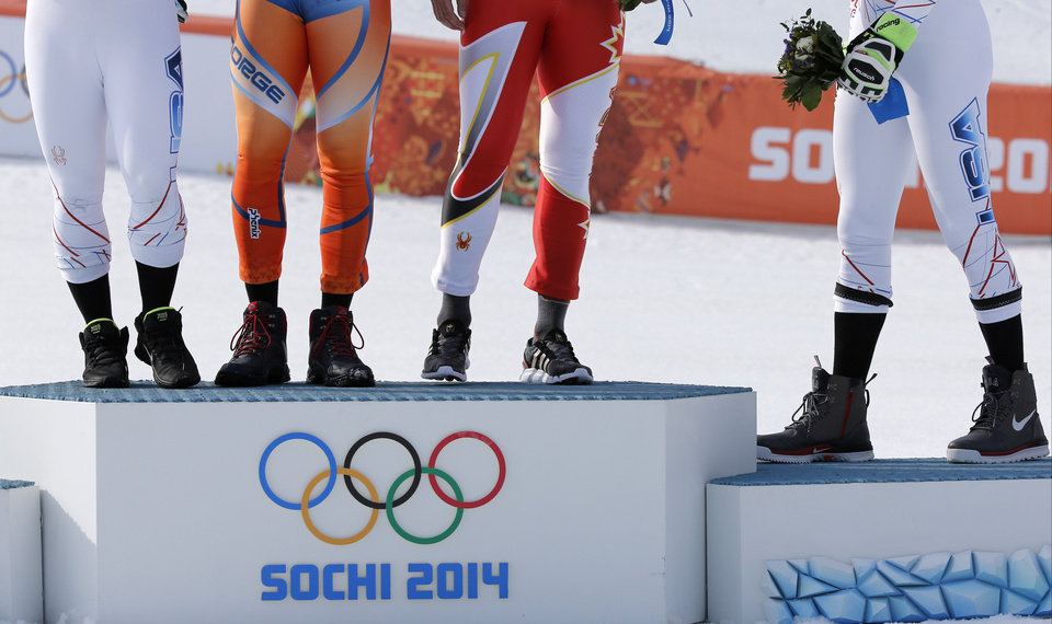 Photo - Men's super-G medalists, from left United States' Andrew Weibrecht (silver), Norway's Kjetil Jansrud (gold), Canada's Jan Hudec (bronze) and United States' Bode Miller (bronze) stand on the podium for a flower ceremony at the Sochi 2014 Winter Olympics, Sunday, Feb. 16, 2014, in Krasnaya Polyana, Russia.(AP Photo/Christophe Ena)