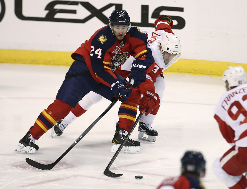 Florida Panthers' Brad Boyes (24) and Detroit Red Wings' Pavel Datsyuk (13) chase the puck during the second period of a NHL hockey game in Sunrise, Fla., Tuesday, Dec. 10, 2013. (AP Photo/J Pat Carter)