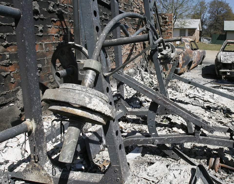 The heat from the fire at this home on 14328 NE 4th St. in Choctaw, Okla., was hot enough to soften and bend this iron barbell.  Saturday, April 11, 2009. Photo by Paul Hellstern, The Oklahoman