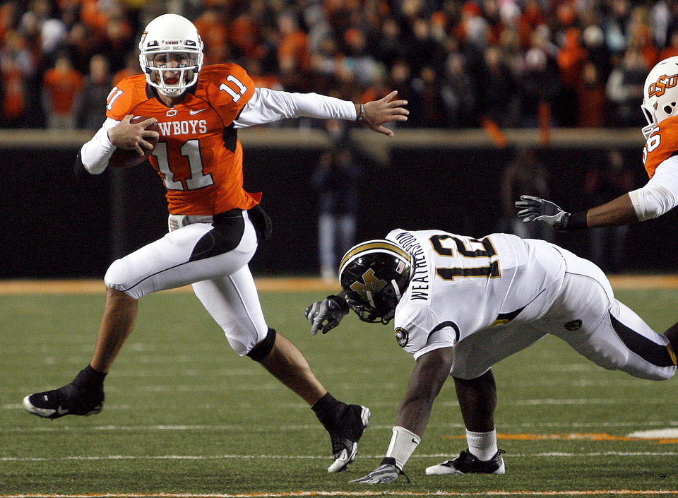 Photo - OSU's Zac Robinson (11) escapes Missouri's Sean Weatherspoon (12)  during the college football game between Oklahoma State University (OSU) and the University of Missouri (MU) at Boone Pickens Stadium in Stillwater, Okla. Saturday, Oct. 17, 2009.  Photo by Sarah Phipps, The Oklahoman