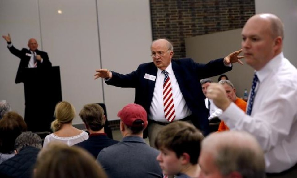Photo -  William Bone, middle, president of National Auction Group Inc., Gadsden, Alabama, looks for bids during an auction of condos at Founders Tower Tuesday night. [PHOTO BY SARAH PHIPPS, THE OKLAHOMAN]