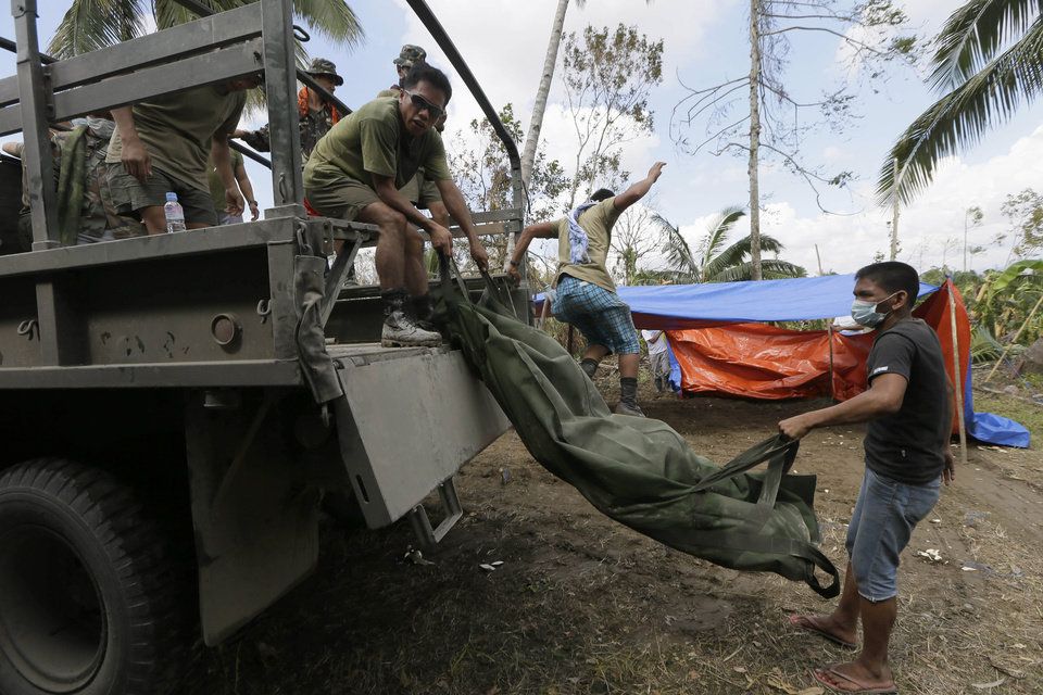 Soldiers unload another victim of typhoon Bopha as retrieval operations continue at the hardest hit New Bataan township, Compostela Valley in southern Philippines Sunday Dec. 9, 2012. The number of missing in the wake of a typhoon that devastated parts of the southern Philippines has jumped to nearly 900 after families and fishing companies reported losing contact with more than 300 fishermen in the South China Sea and Pacific Ocean, officials said Sunday. (AP Photo/Bullit Marquez)