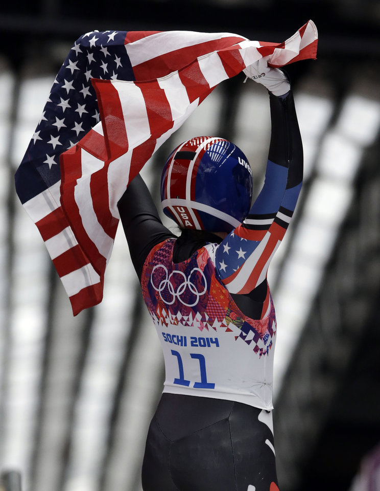 Photo - Erin Hamlin of the United States waves the flag to the crowd after finishing her final run to win the bronze medal during the women's singles luge competition at the 2014 Winter Olympics, Tuesday, Feb. 11, 2014, in Krasnaya Polyana, Russia. (AP Photo/Dita Alangkara)