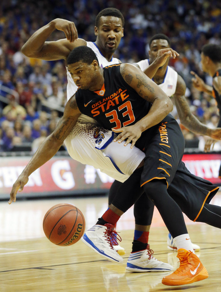 Photo - Oklahoma State guard Marcus Smart (33) is fouled by Kansas guard Wayne Selden, Jr., back, during the first half of an NCAA college basketball game in the quarterfinals of the Big 12 Conference men's tournament in Kansas City, Mo., Thursday, March 13, 2014. (AP Photo/Orlin Wagner)
